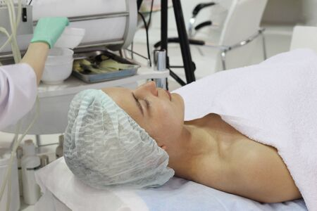 A young woman is lying on the cosmetic bed in the beauty salon. A woman is ready for rejuvenating facial treatments. Peeling face in the beauty parlor. Banque d'images - 133376752