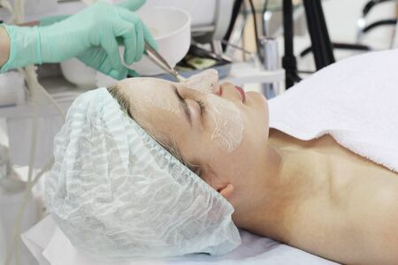 In the beauty salon a young woman is doing a peeling on her face. Anti-aging procedures on the face. Dermatologist. Banque d'images - 133376756
