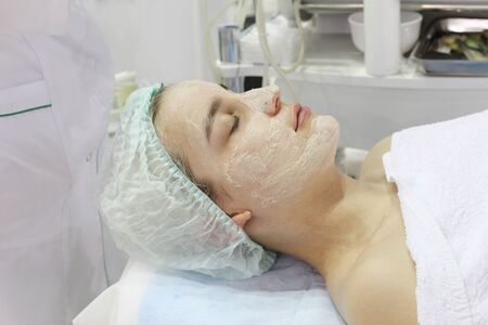 In the beauty salon a young woman is doing a peeling on her face. Anti-aging procedures on the face. Dermatologist. Banque d'images - 133376757