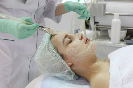 In the beauty salon a young woman is doing a peeling on her face. Anti-aging procedures on the face. Dermatologist. Banque d'images - 133376767
