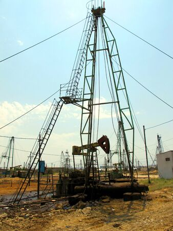 Abandoned oil rigs. Jacks of the oil pump. Machines for the extraction of crude oil in the field.