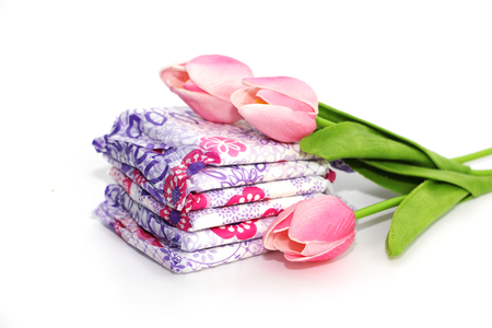 Feminine sanitary pads in the package on a white background. Gaskets for monthly use with colors. Photos are decorated with three tulips. Standard-Bild