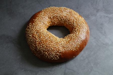 One fresh bagel with sesame seeds. On a vintage background. Tasty breakfast.