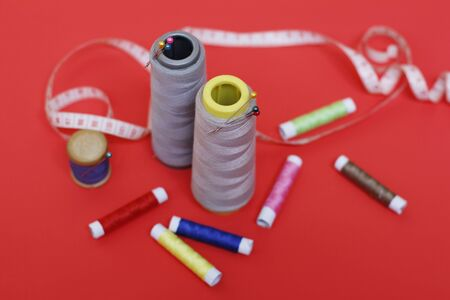 Composition with threads and sewing accessories on a red background. Sewing supplies and needlework accessories. Spools of thread, scissors and needles on a red background.