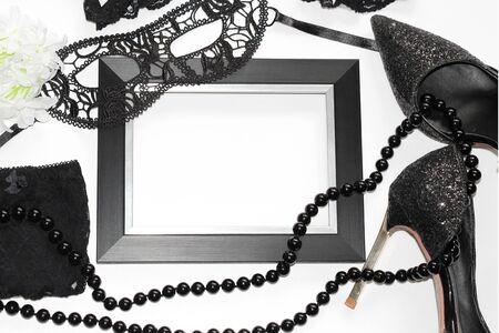 Flat Lay. Still life. Black female things on a white background. Sexual wardrobe items. Photo for magazines and postcards. Lace underwear.