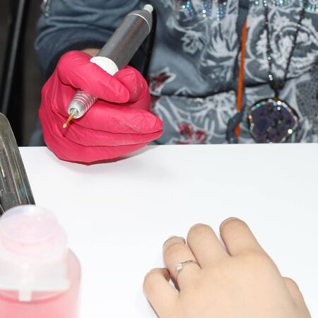 Hardware manicure. Finger treatment of nails. Electric nail file in action. Closeup of the hands of a beautician in red gloves. The master removes the cuticle using a hardware manicure method.