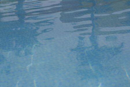 Ripple of pool water with sun reflection. Blue pool rippled water. Stock Photo