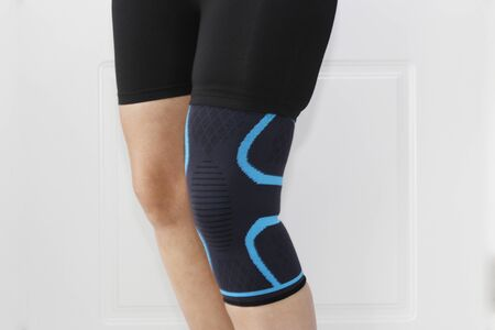 Closeup of a leg with one grip of a knee brace. Orthopedic knee pad. A woman wears a knee brace. Knee joint problem.
