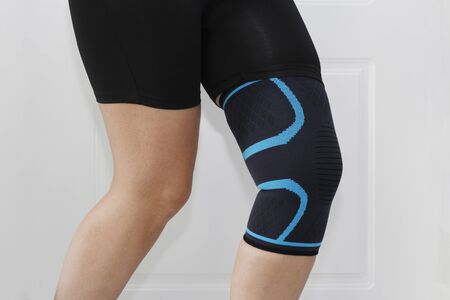 Elastic bandage on the knee. Elastic anatomical knee pad after knee injury. Sprain of the knee.