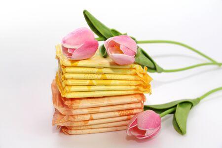 Serviettes hygiéniques féminines dans l'emballage. De nombreuses serviettes hygiéniques en emballage individuel. Serviettes pour femmes à usage mensuel. La photo est décorée de trois tulipes.