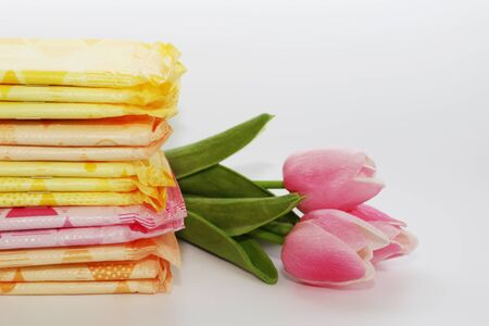 Feminine sanitary pads in the package. Many sanitary pads in individual packaging. Womens pads for monthly use. The photo is decorated with three tulips.