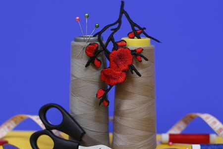 Two large spools of thread stand on a blue background. In the photo there is an application in the form of red flowers, scissors for sewing, buttons and tape measure. Needlework concept. Stok Fotoğraf