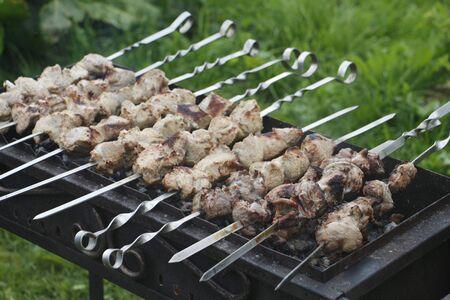 Cooking barbecue skewers. Marinated kebab is grilled on charcoal. Shish kebab was made of lamb, pork, beef, chicken. Roast beef skewers on barbecue grill. Skewers on skewers.