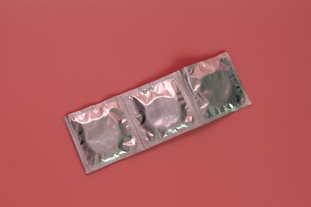 Three condoms in foil packaging on a pink background. There is nothing else. There is a place for text. Safe sex concept.