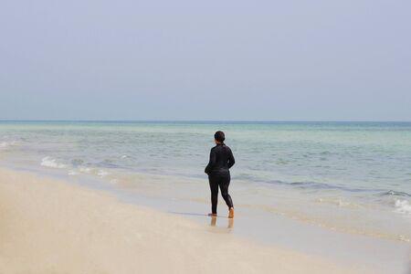 One Muslim woman is walking along the beach. The girl is dressed in black beachwear.