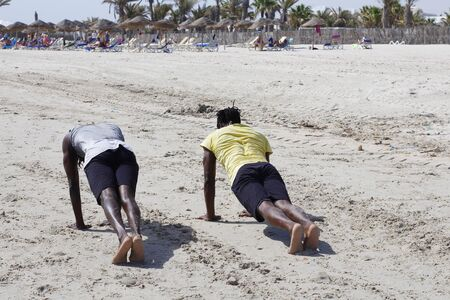 Two African American men play sports on the beach. Exercise on the beach. Banco de Imagens