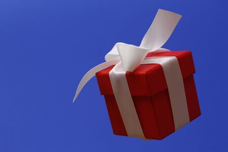 Red gift box with a white bow on a blue background. The box is closed by a lid. Gift flies in the air.