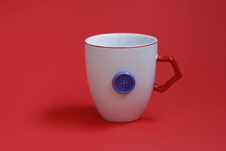 White mug with a red pen on a red background. The mug has a decor - a blue button. Concept - a mug for a seamstress and needlewomen. Stok Fotoğraf
