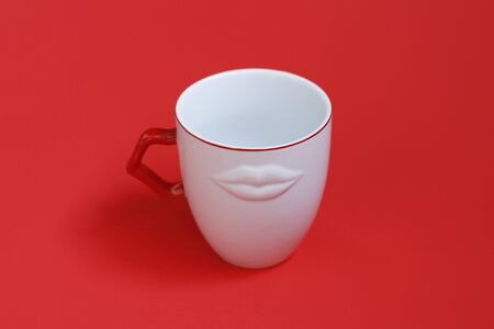 White mug with a red pen on a red background. The mug has decor - white lips. Concept - a mug for a close friend, a kiss symbol.