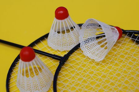Badminton. Three shuttlecocks and two badminton rackets. Colored yellow background. Idea for a magazine. Healthy lifestyle concept.