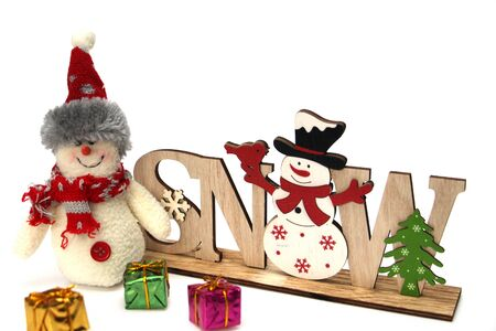 Christmas wooden decoration with a snowman and the inscription SNOW. Nearby are many colorful gift boxes and a large rag snowman. Decor for home decoration. White background. Stok Fotoğraf