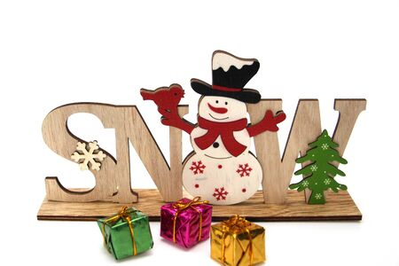 Christmas wooden decoration with a snowman and the inscription SNOW. A lot of multi-colored gift wrapping. Christmas and New Year decor for home decoration. White background.