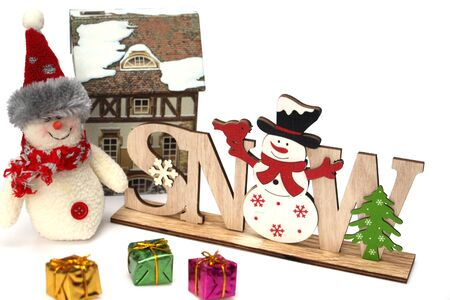 Christmas wooden decoration with a snowman and the inscription SNOW. Nearby are multi-colored gift boxes, a large rag snowman, a clock, a hut. Decor for home decoration. White background. 版權商用圖片