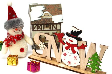 Christmas wooden decoration with a snowman and the inscription SNOW. Nearby are multi-colored gift boxes, a large rag snowman, a clock, a hut. Decor for home decoration. White background. Stok Fotoğraf