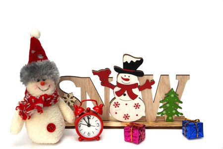 Christmas wooden decoration with a snowman and the inscription SNOW. Nearby are multi-colored gift boxes, a large rag snowman and a watch. Decor for home decoration. White background.