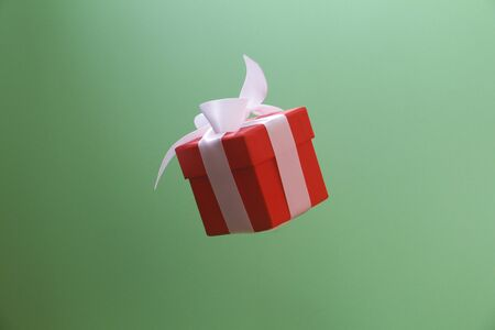 Red gift box with a white bow on a green background. The box is closed by a lid. A gift flies in the air. Levitation.