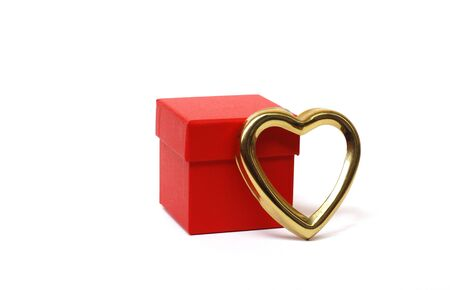 Red gift box with a closed lid on a white background. There is a place for text. Bright red box without inscriptions. Nearby is a golden heart. Gift for Valentines day. Stok Fotoğraf