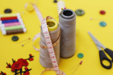 Sewing buttons and threads on a yellow background. Needlework concept. A lot of multi-colored little bobbins of sewing thread on a yellow background. Skeins of thread for needlework and sewing. Stockfoto