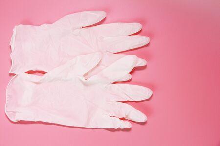 Zwei weiße medizinische Handschuhe auf rosa Hintergrund. Sterile Latexhandschuhe. Medizinischer Handschuh zum Schutz und zur Patientenversorgung. Rosa Hintergrund. Standard-Bild