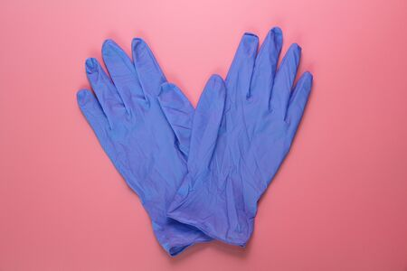 Two blue medical gloves on a pink background. Sterile latex gloves. Medical glove for protection and patient care. Pink background.