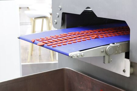 On the automatic conveyor of industrial production are sausages. Meat industry. Automated production lines for the formation of cutlets. Conveyor equipment at the grocery factory.