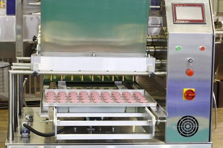 Making sweet cakes on a production line. A baking machine with a conveyor on which confectionery is located. The operation of the machine is shown. Molding system. Stock Photo