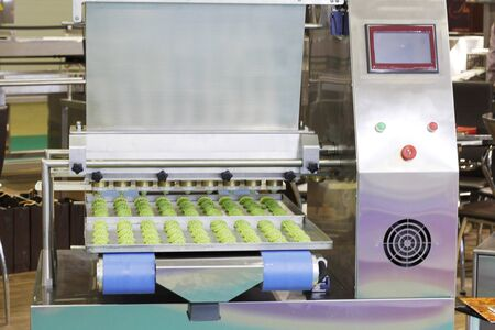 Making sweet cakes on a production line. A baking machine with a conveyor on which confectionery is located. The operation of the machine is shown. Molding system.