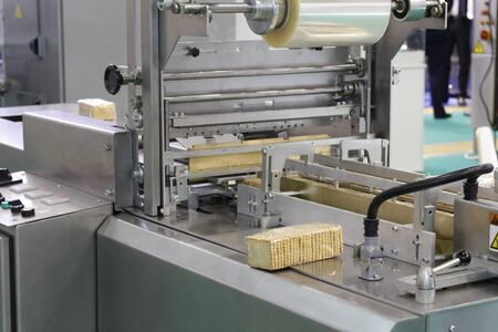 Automatic packing machine. Filling equipment. Packing in a transparent cellophane film. Designing machines for the food industry. Imagens