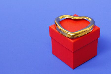 Red gift box with a closed lid on a blue background. There is a place for text. Bright red box without inscriptions. Nearby is a golden heart. Valentines Day Gift.