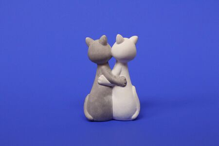 Two cats are hugging. Cats are close and love each other. Valentines Day. Figurine cats in love. Cats together are a symbol of lovers. Congratulation. Place for text. Blue color. Imagens