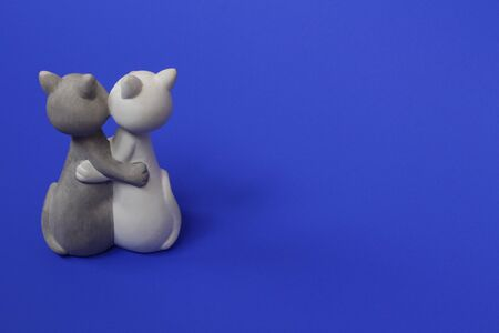 Two cats are hugging. Cats are close and love each other. Valentines Day. Figurine cats in love. Cats together are a symbol of lovers. Congratulation. Place for text. Blue color. Banque d'images - 136992675