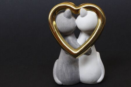 Two cats are hugging. Cats are close and love each other. Valentines Day. Figurine cats in love. Nearby is a golden heart. Cats together are a symbol of lovers. Congratulation. Banque d'images - 136994131