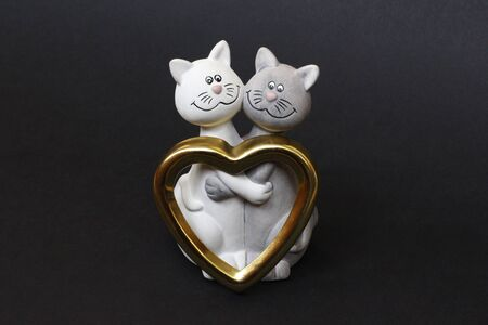 Two cats are hugging. Cats are close and love each other. Valentines Day. Figurine cats in love. Nearby is a golden heart. Cats together are a symbol of lovers. Congratulation.