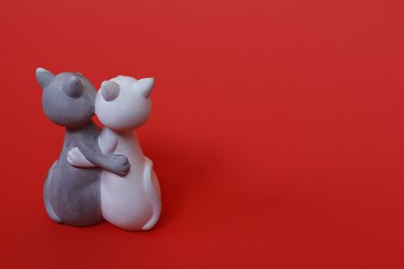 Two cats are hugging. Cats are close and love each other. Valentines Day. Figurine cats in love. Cats together are a symbol of lovers. Congratulation. Place for text.