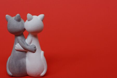 Two cats are hugging. Cats are close and love each other. Valentines Day. Figurine cats in love. Cats together are a symbol of lovers. Congratulation. Place for text. Banque d'images - 136999873