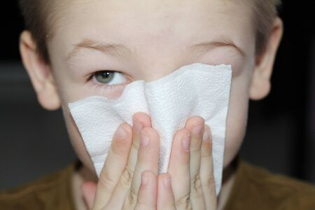 Moscow, FR, 01.26.2019: The boy wipes his nose with a napkin. The child blows his nose. The kid is sick with allergy symptoms. Young cute boy blows his nose in a paper napkin.