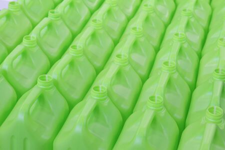 A lot of bottles without lids made of green plastic. Manufacture of plastic products. Texture for the background. The concept of plastic products. Clean containers in green. Foto de archivo