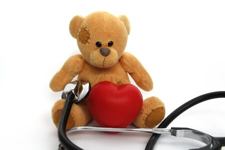 Teddy bear with a red heart on a white background. A teddy bear holds a big heart in his hands. Nearby is a stethoscope. Healthy lifestyle concept.