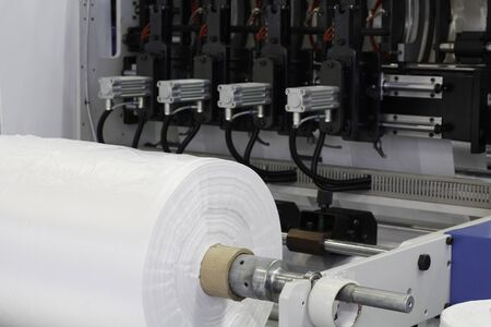 A fragment of a machine for the production of plastic bags. The production of plastic bags at the factory. The shafts are spinning. Cellophane moves between the shafts.