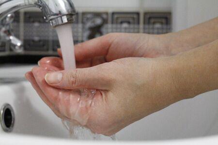 Hand washing. Wash hands under running water. Hygiene concept and virus prevention. Close up of female hands. Hand washing in the bathroom. COVID-19. Coronavirus. Coronavirus infection.